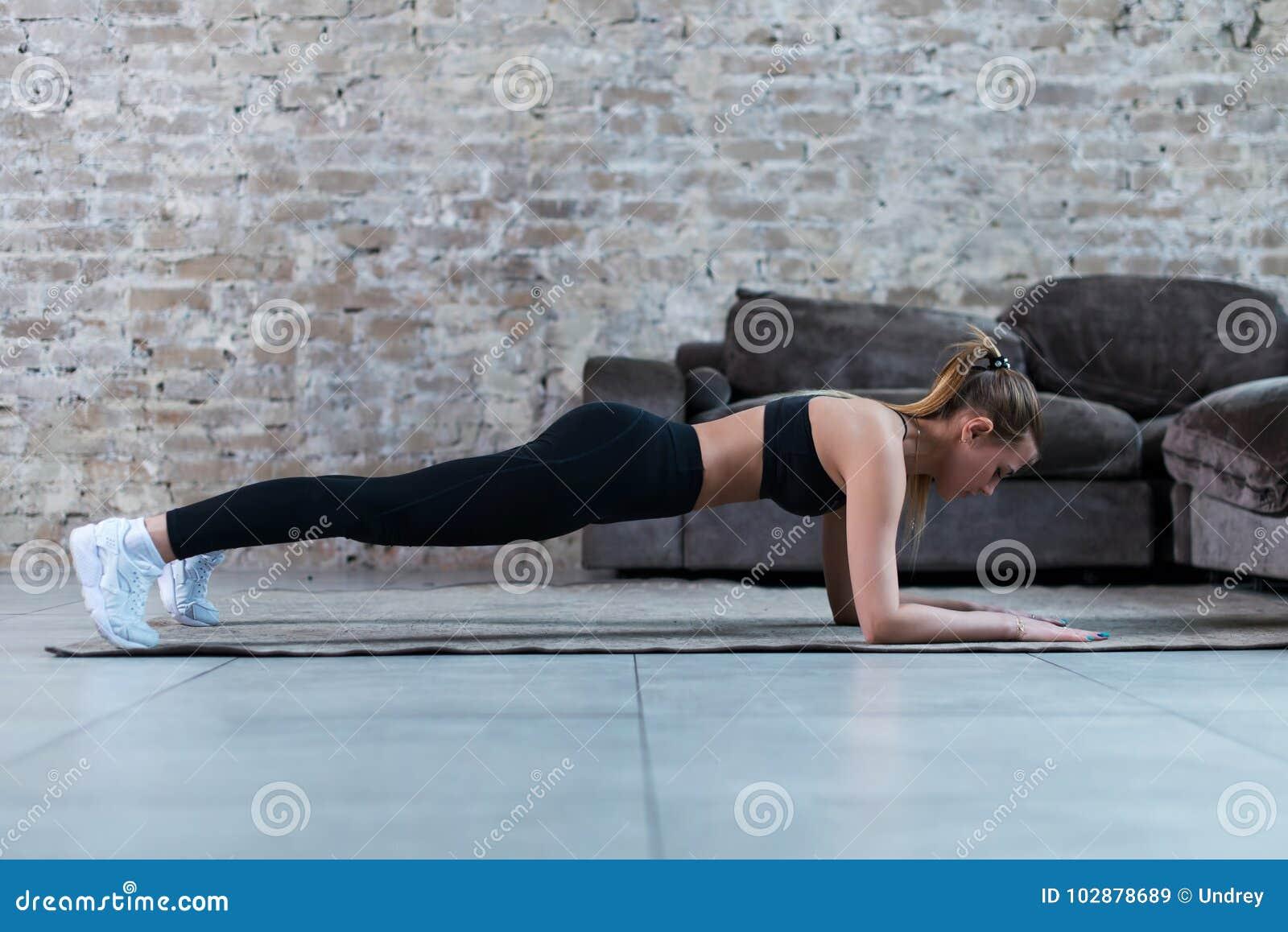 Het slanke jonge brunette die zwarte gymnastiekkleding dragen die buikbrug of voorplank doen oefent in zolderflat uit