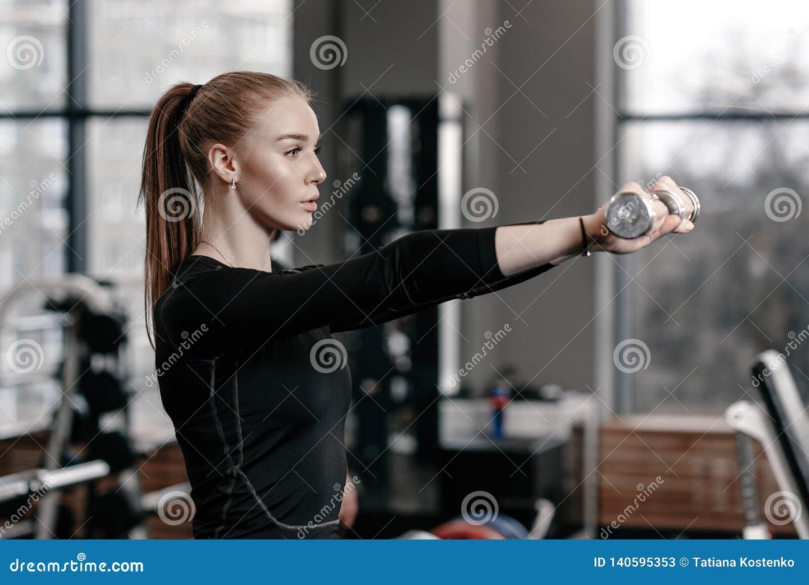 Het slanke jonge meisje gekleed in een zwarte sportkleding doet oefeningen met domoren in de moderne gymnastiek met veel sport