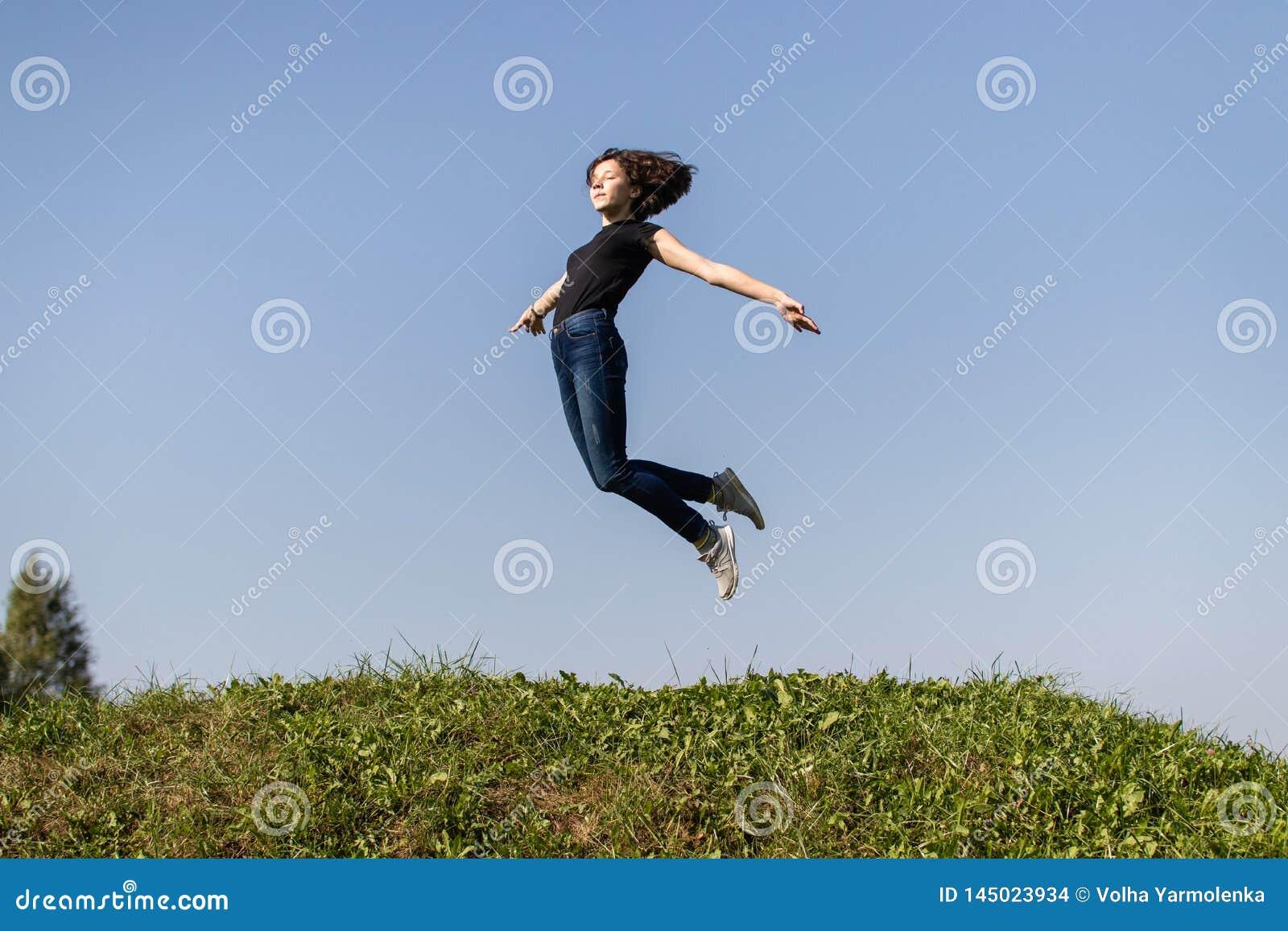 Het slanke tienermeisje kleedde zich in jeans en een zwarte bovenkant hoog springend over groen gras tegen de hemel