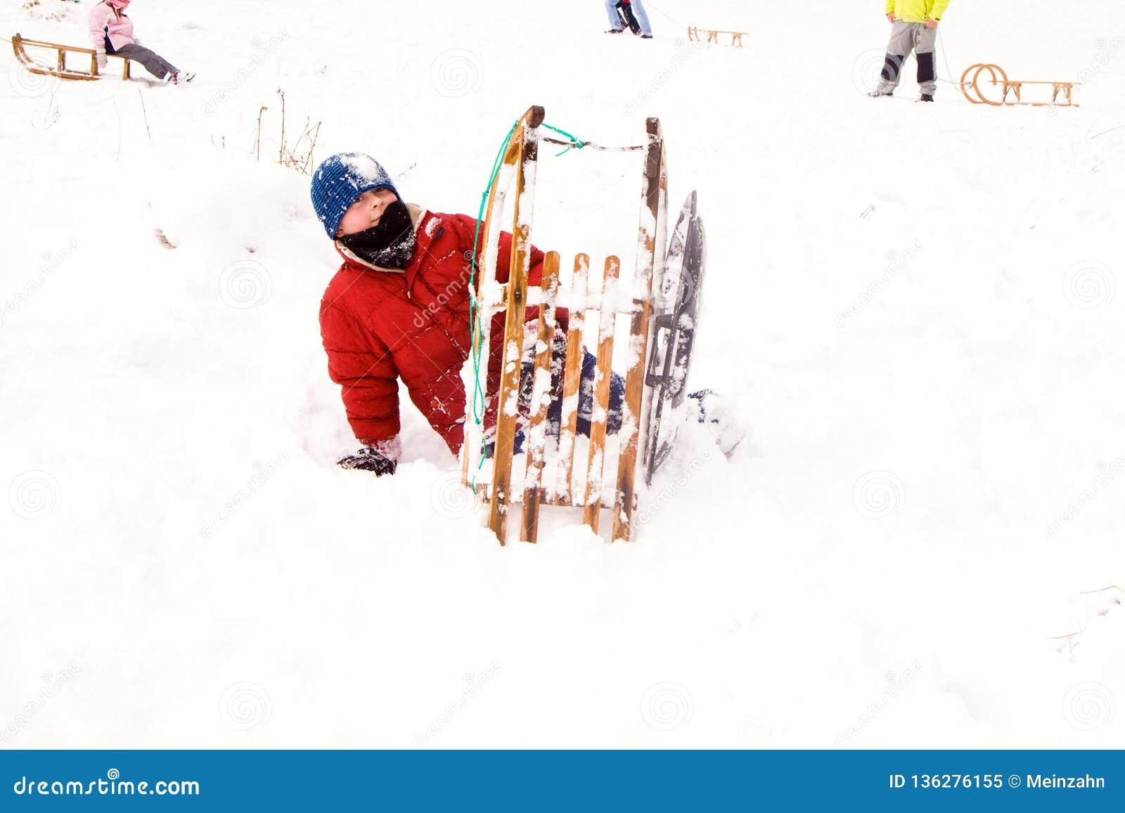 Het sledding van het kind onderaan de heuvel in sneeuw, de witte winter