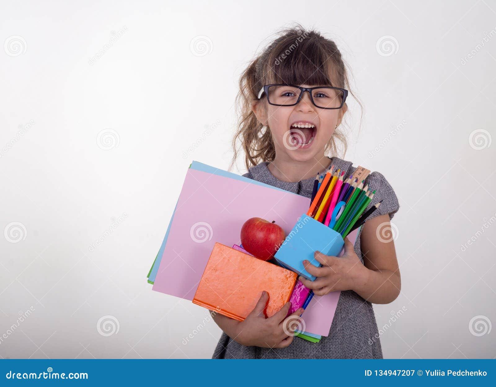 Het slimme kind in oogglazen het houden trekt en schildert levering Jonge geitjes gelukkig om naar school terug te keren