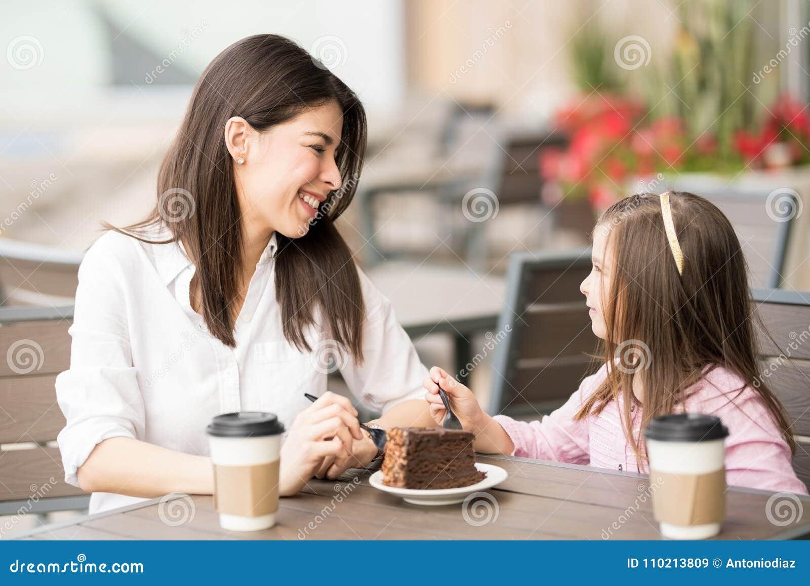 Het Spaanse donkerbruine spreken met een klein meisje in een koffie