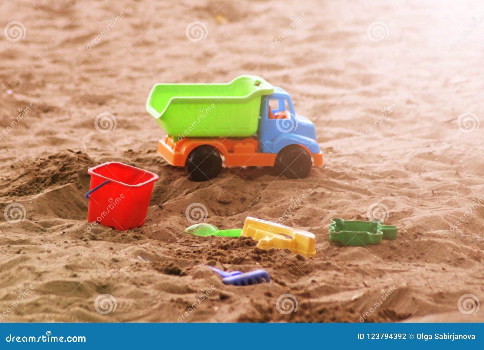Het speelgoed van het kinderen` s strand - emmers, spoor en schop op zand op een zonnige dag