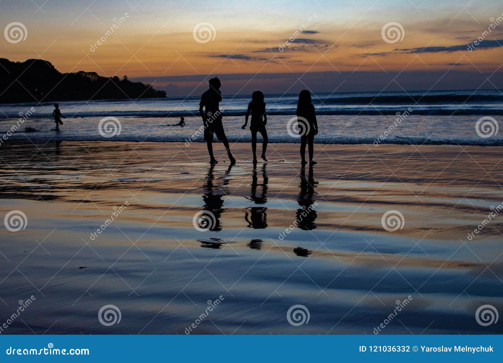 Het spel van kinderen op zonsondergang Indische Oceaan