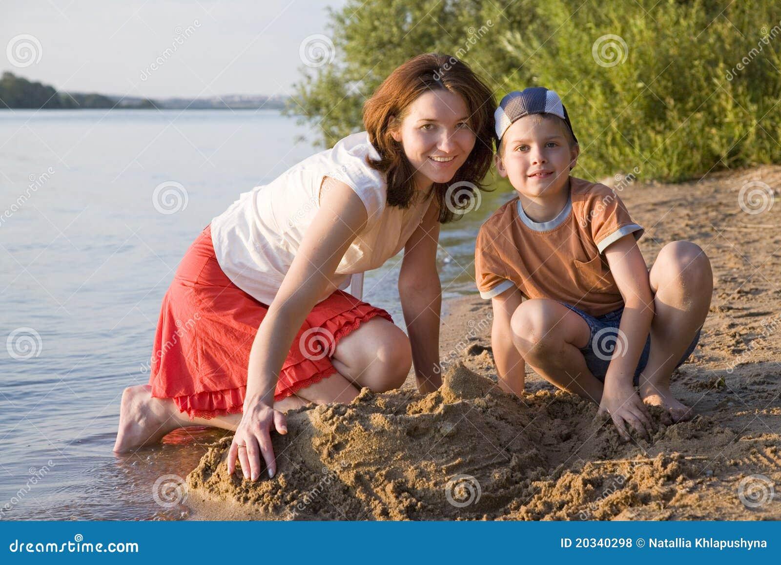 Het spelen van de moeder en van de zoon in het zand