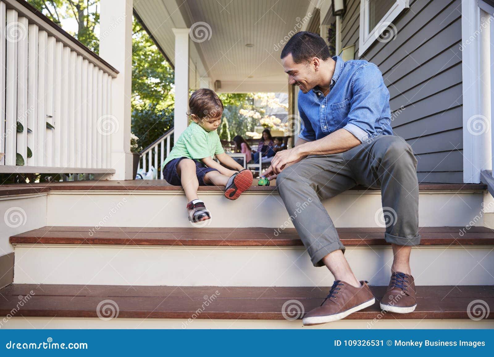 Het Spelen van vaderand son Sit On Porch Of House met Speelgoed samen