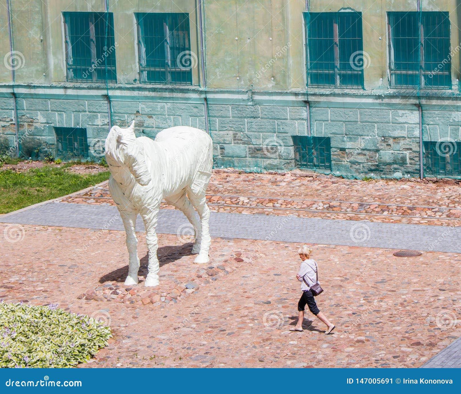 Het Spook van de Dinaburg-vesting is een wit paard Zij draaide haar hoofd aan het meisje die overgaan door