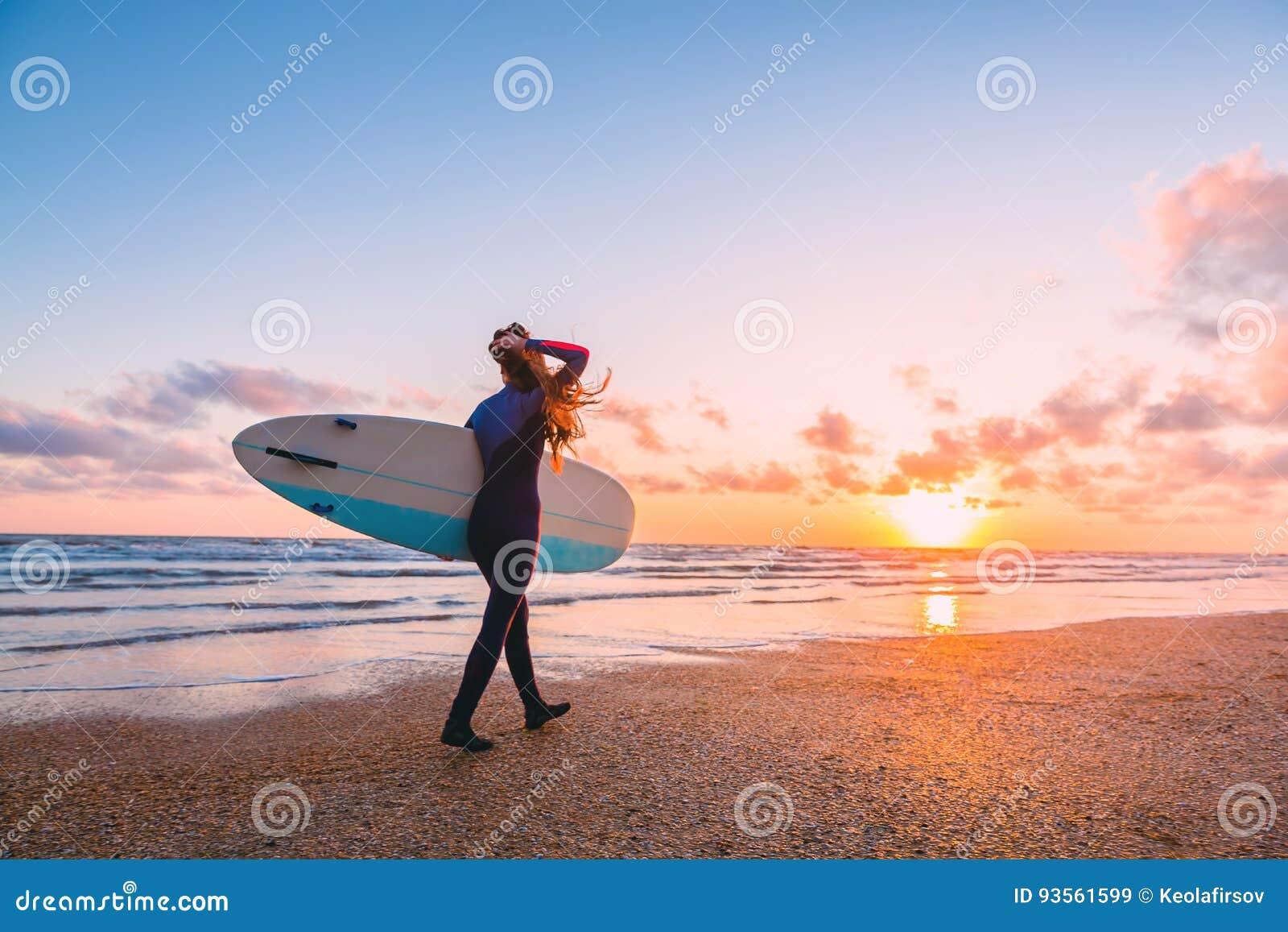 Het sportieve brandingsmeisje gaat naar het surfen Vrouw met surfplank en zonsondergang of zonsopgang op oceaan