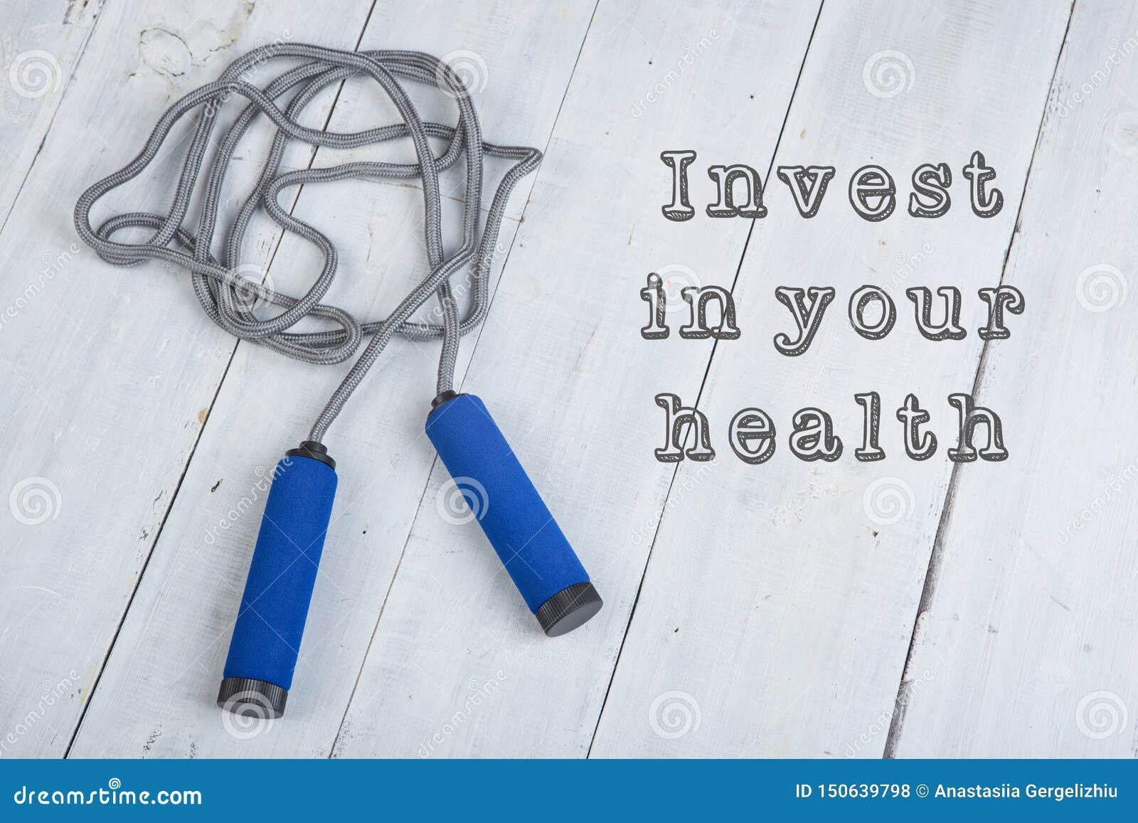 Het springen/het touwtjespringen met blauwe handvatten op witte houten achtergrond met tekst investeert in uw gezondheid