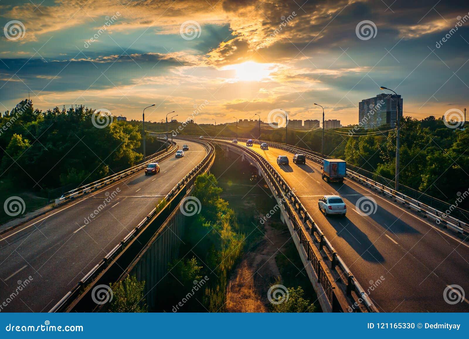 Het stadsverkeer op asfaltweg of de wegroute in zonsondergangtijd, partij van auto s drijft met snelle snelheid, stedelijke vervo