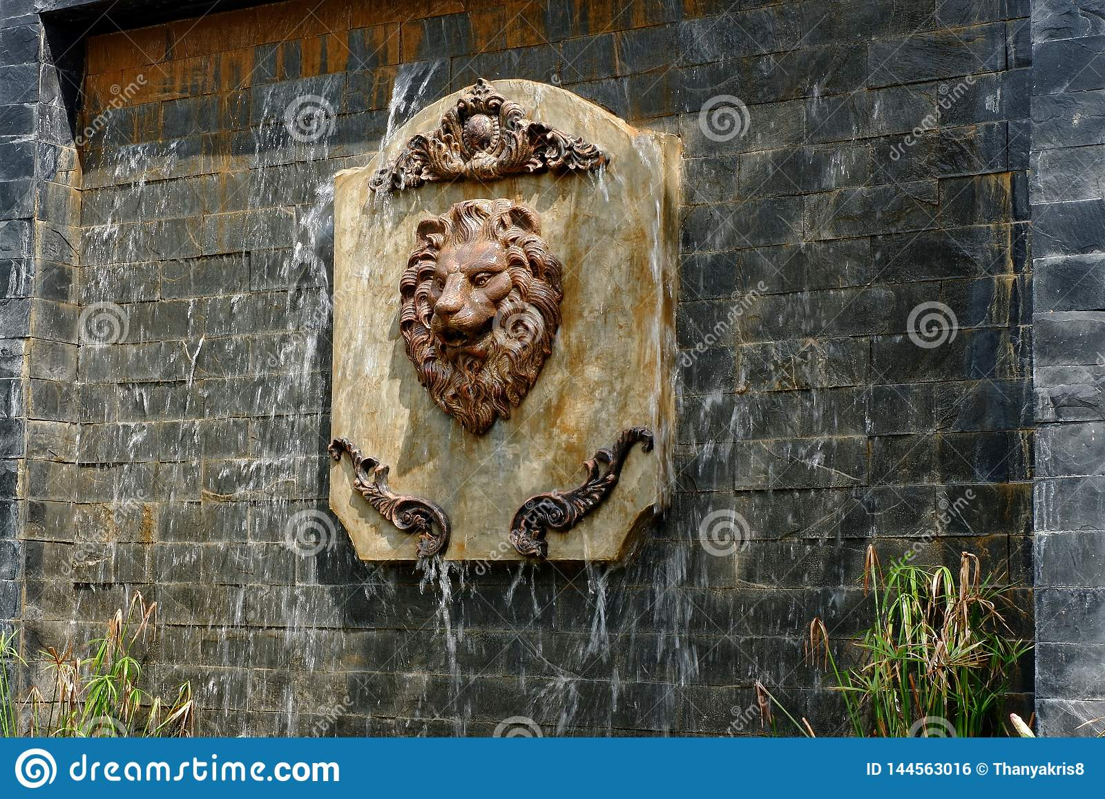 Het standbeeld van een leeuwgezicht in een replicawaterval