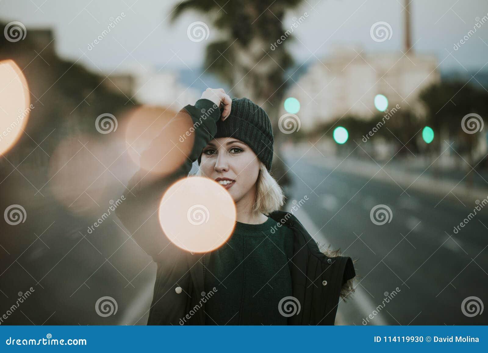 Het stedelijke portret van blondevrouw met breit hoed in het midden van de straat met lichten