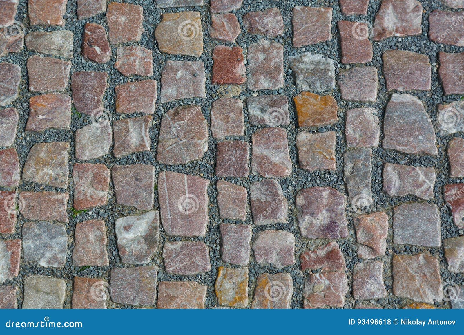 Het steengraniet cobblestoned bestratingsachtergrond of textuur Abstracte achtergrond van het oude close-up van de keibestrating