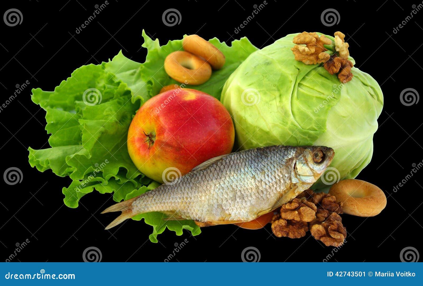 Het stilleven van sla, kool, gedroogd fruit, appel, drogende, droge vis, noten en droog apricotsIsolated op zwarte achtergrond