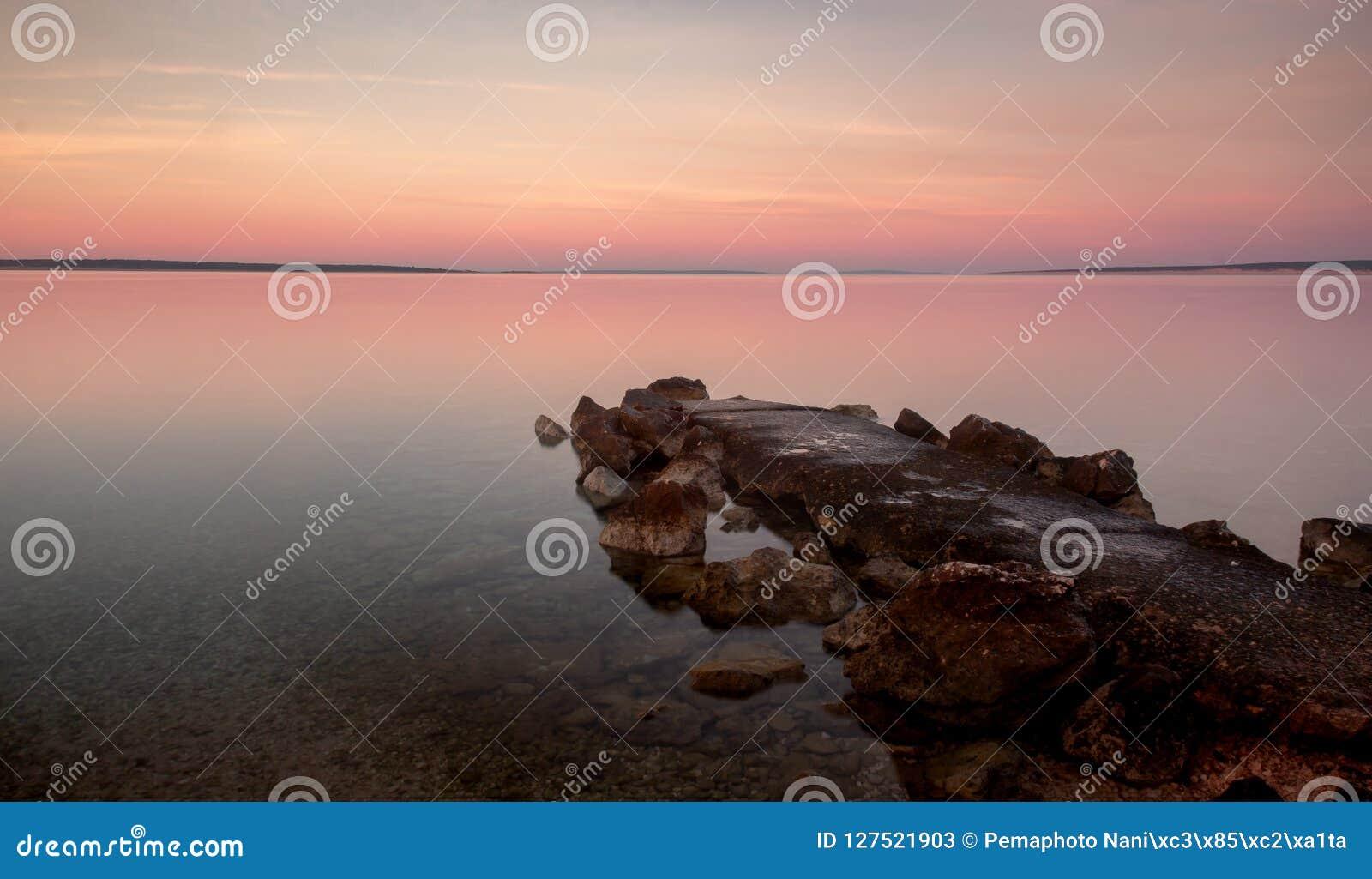 Het Strand van zonsopgangkroatië met Pastelkleur Rocky Jetty