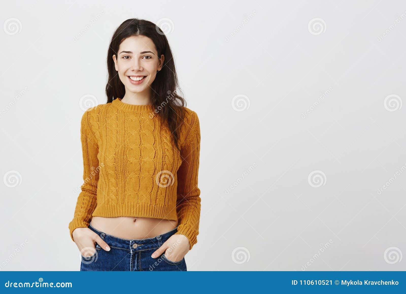 Het studioportret van het charmeren van Kaukasische vrouw die in bebouwde sweater terwijl holding dient zakken, het uitdrukken gl