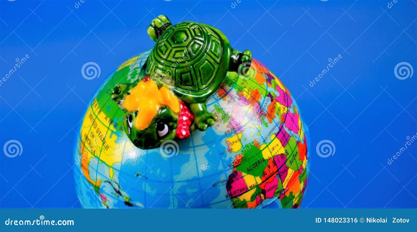 Het stuk speelgoed van kinderen cijfer - schildpad op de bol van de Aarde Het stuk speelgoed is een verminderd model van een fict