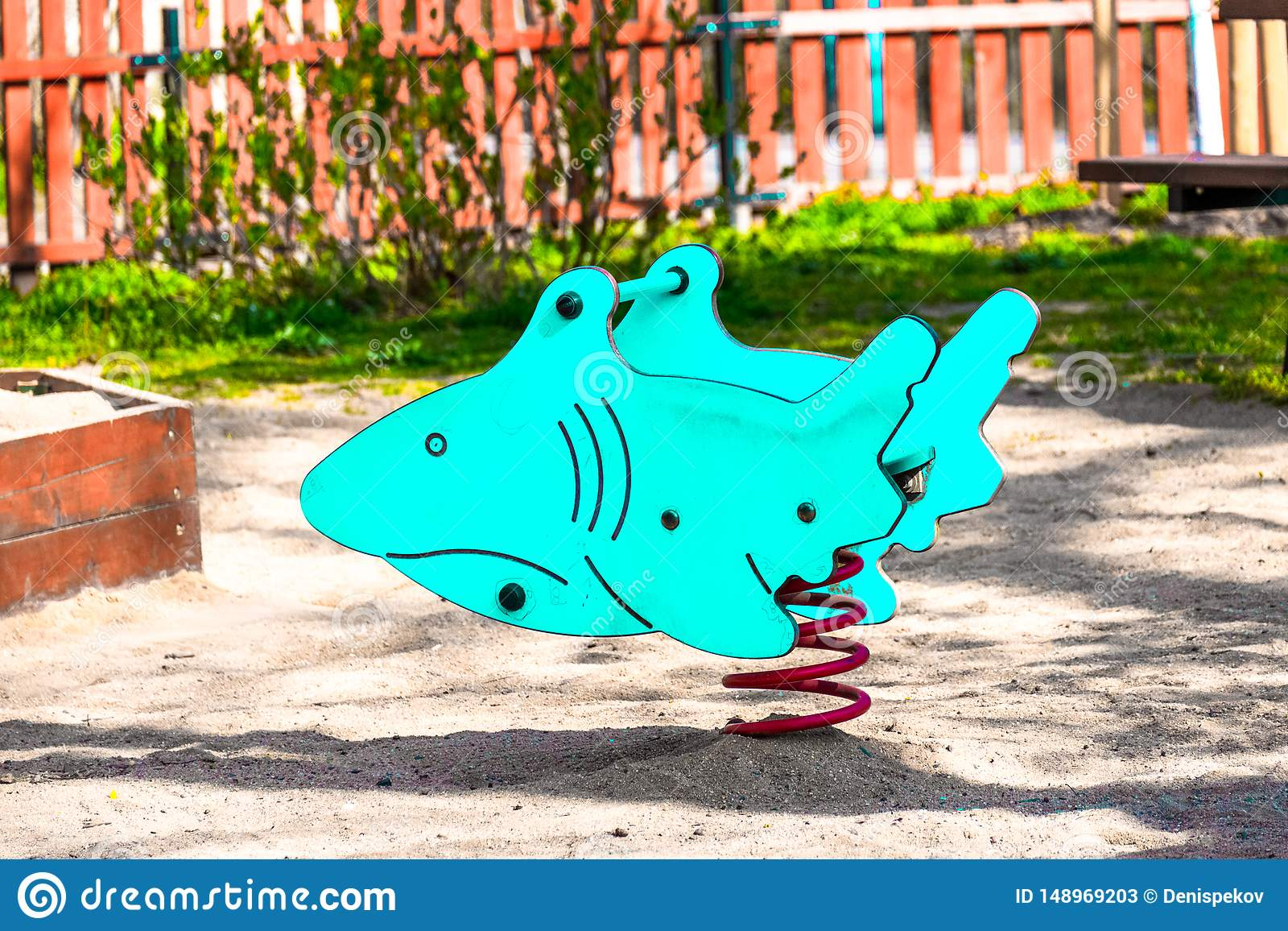 Het stuk speelgoed van kinderen haai, blauwe kleur, op de speelplaats voor kinderen