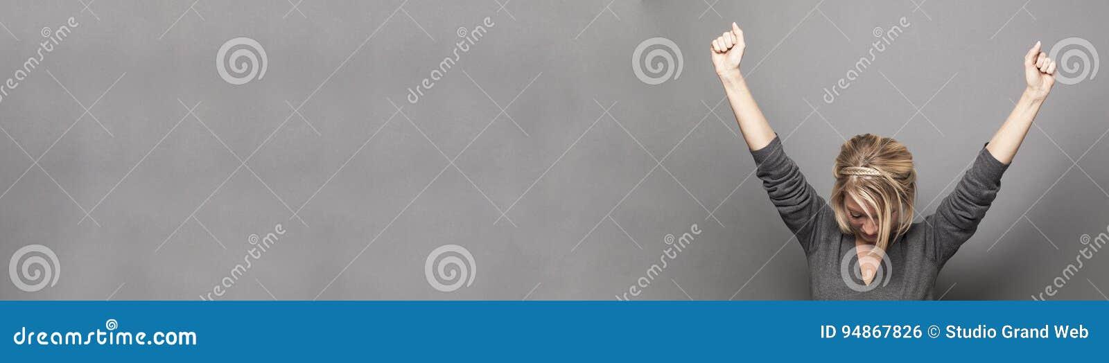 Het succesvolle jonge vrouw winnen met beide omhoog wapens, exemplaarruimte