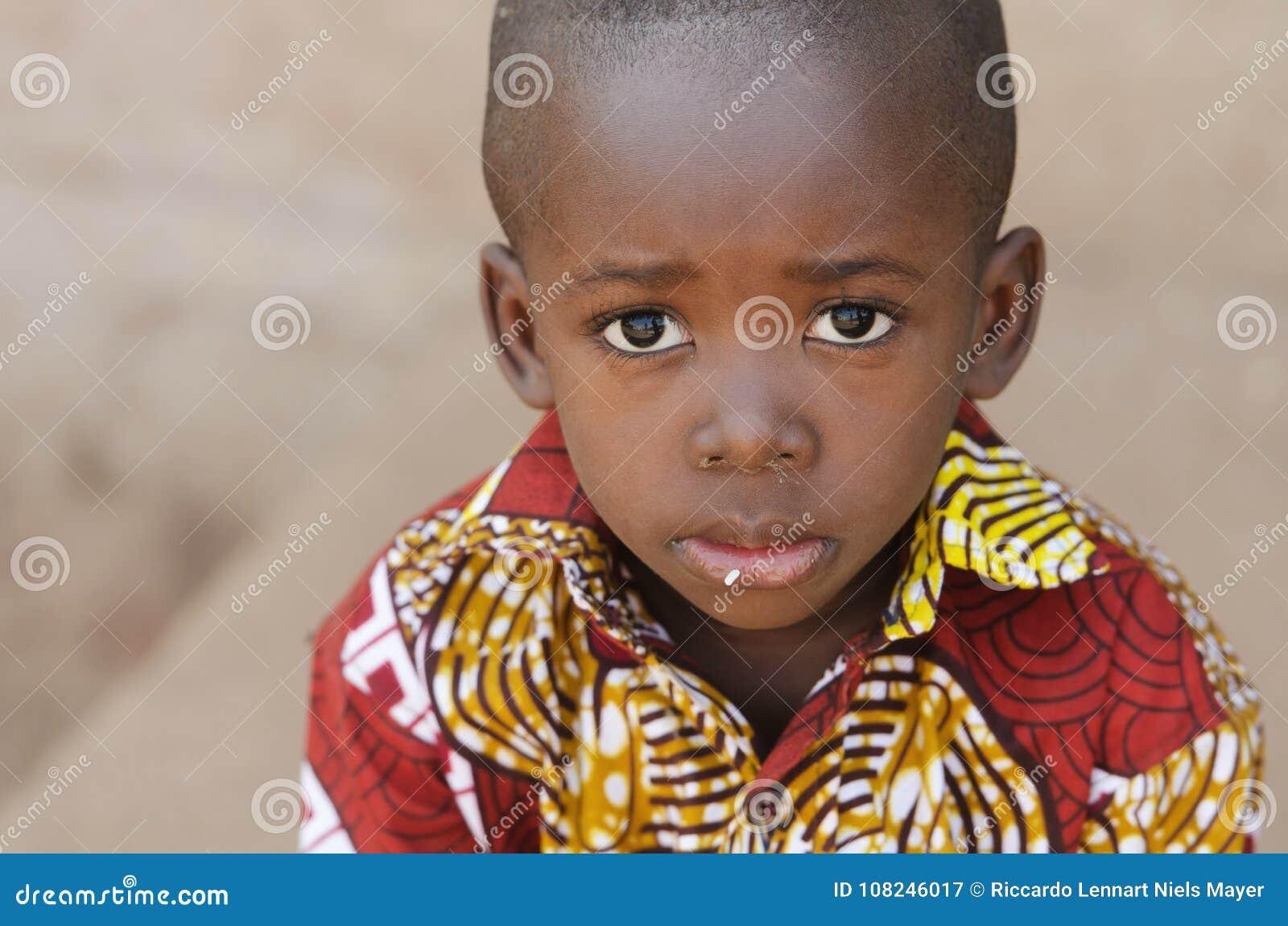 Het Symbool van hongerafrika - Weinig Afrikaanse Jongen met Rijst op Mond