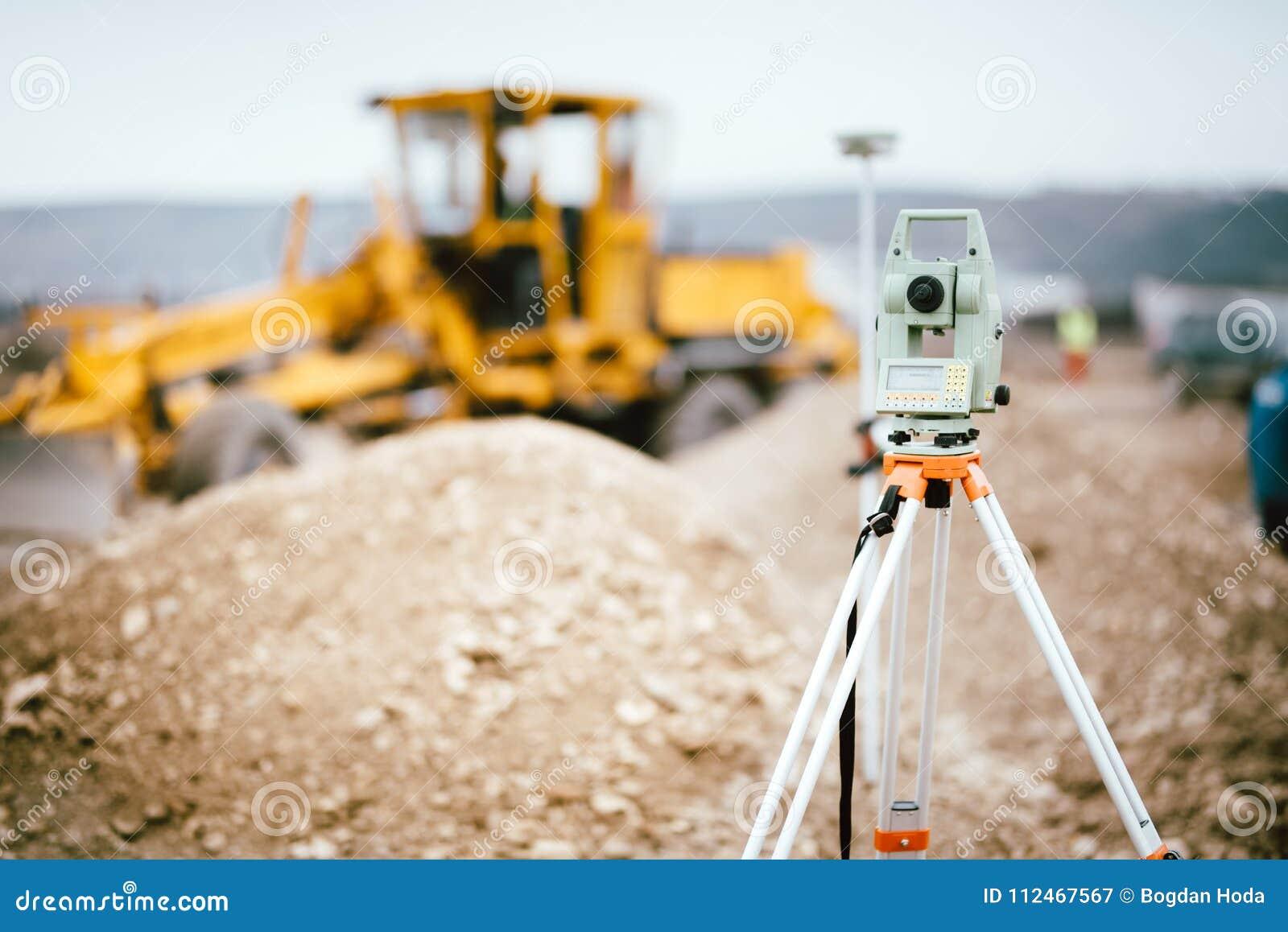 Het systeem of de theodoliet van GPS van het landmetersmateriaal in openlucht bij wegbouwwerf Landmeterstechniek met totale post