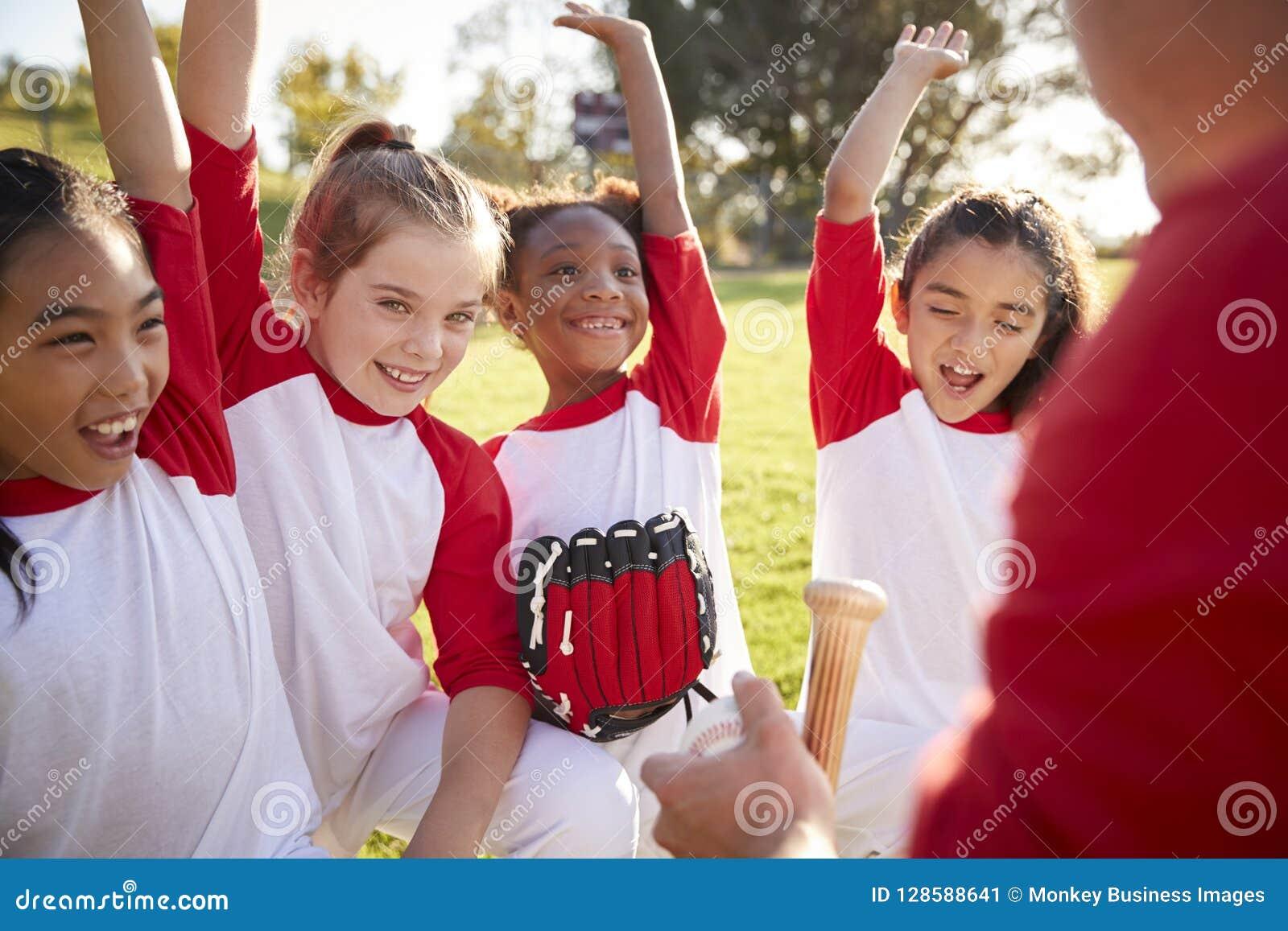 Het team van het meisjeshonkbal in een wirwar met de bus, die handen opheffen