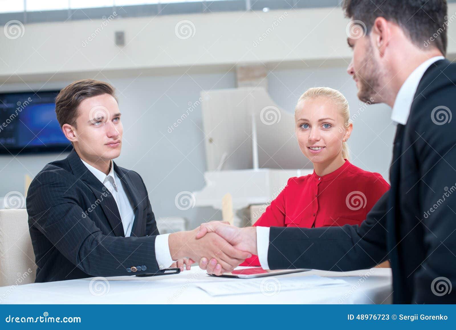 Het team van zakenlieden werkt aan de project en het schudden handen