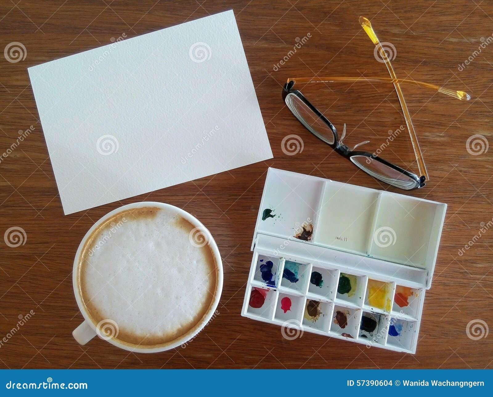 Het tekeningsdocument met waterverfplaat en de hete koffie leggen op de lijst