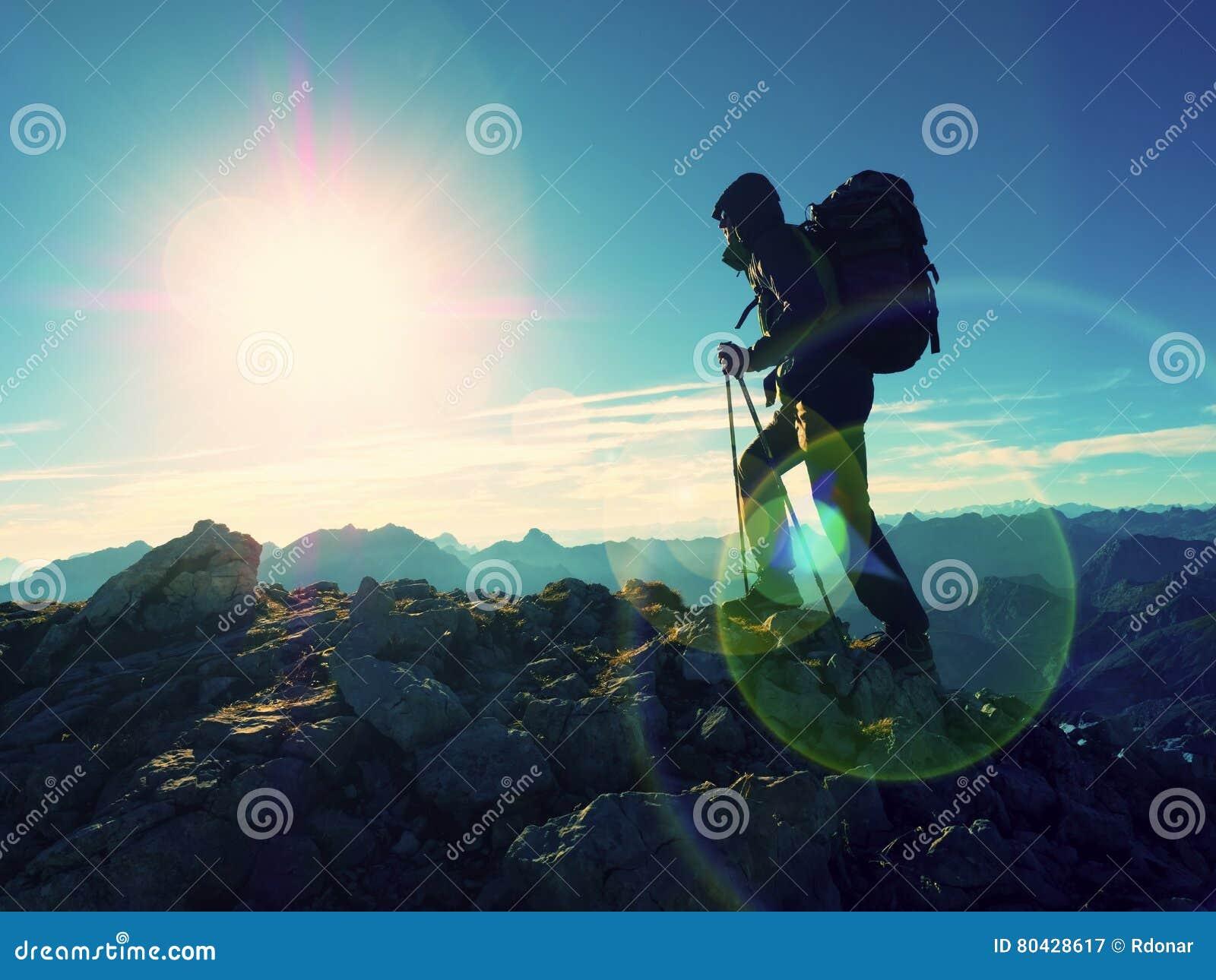 Het tekort van de lensgloed Toeristengids op trekkingsweg met polen en rugzak Ervaren wandelaar