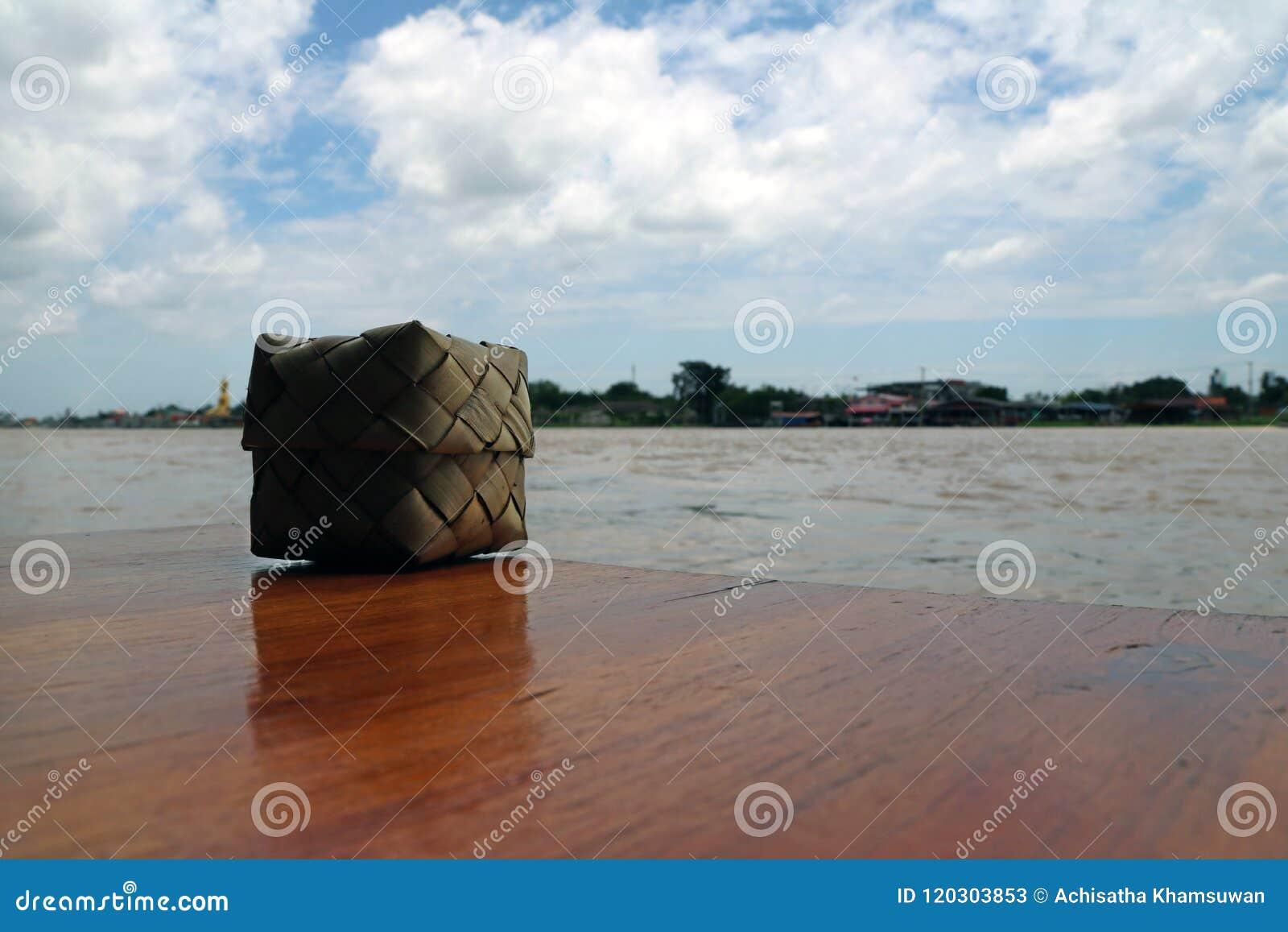 Het Thaise rijs van Kleverige die rijst maakte van kokosnotenblad op de houten lijst, naast Chaophraya-Rivier wordt geplaatst