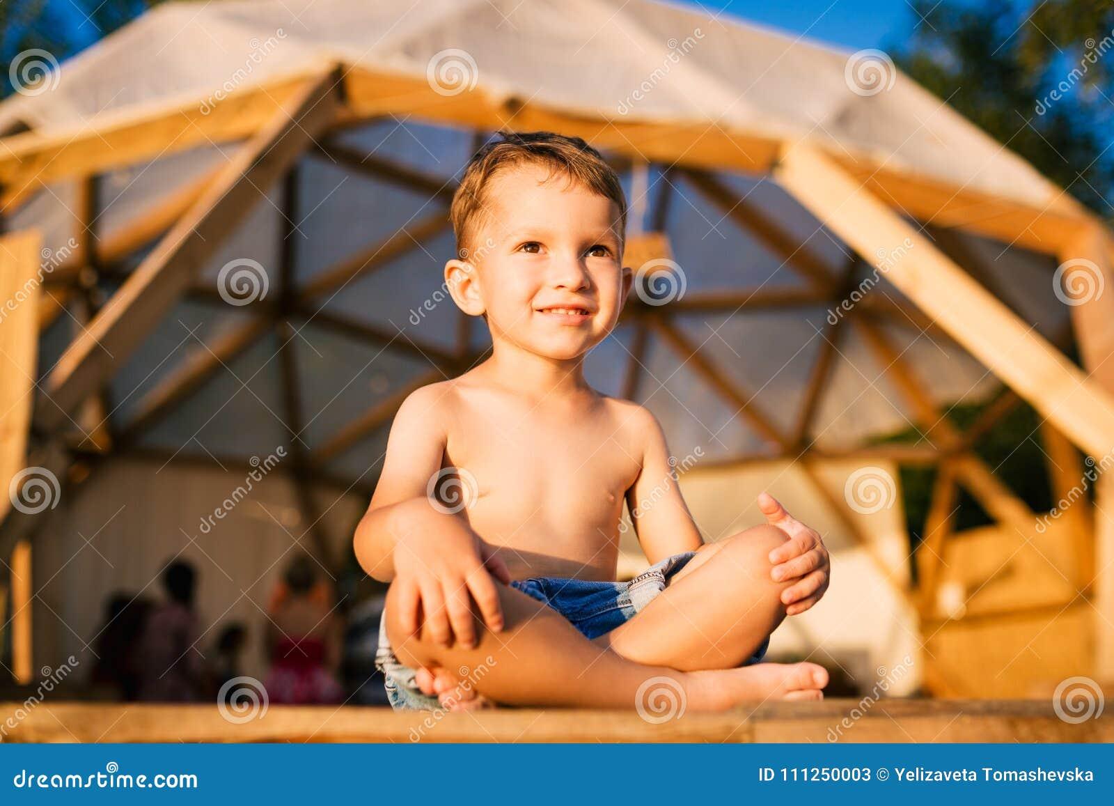 Het thema is yoga en kinderen Kaukasisch Jongenskind die blootvoets met de benen over elkaar in lotusbloempositie zitten inzake h