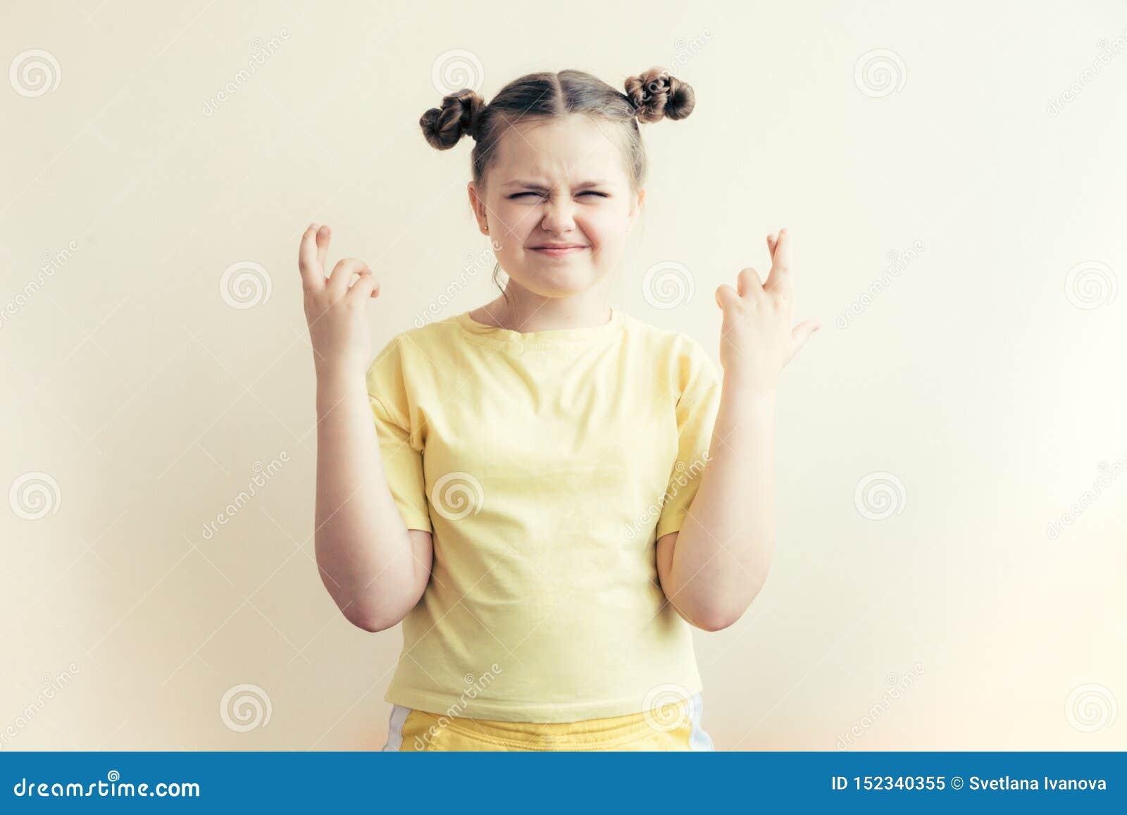 Het tienermeisje kruiste haar die vingers en drukte ogen in afwachting van geluk worden gesloten