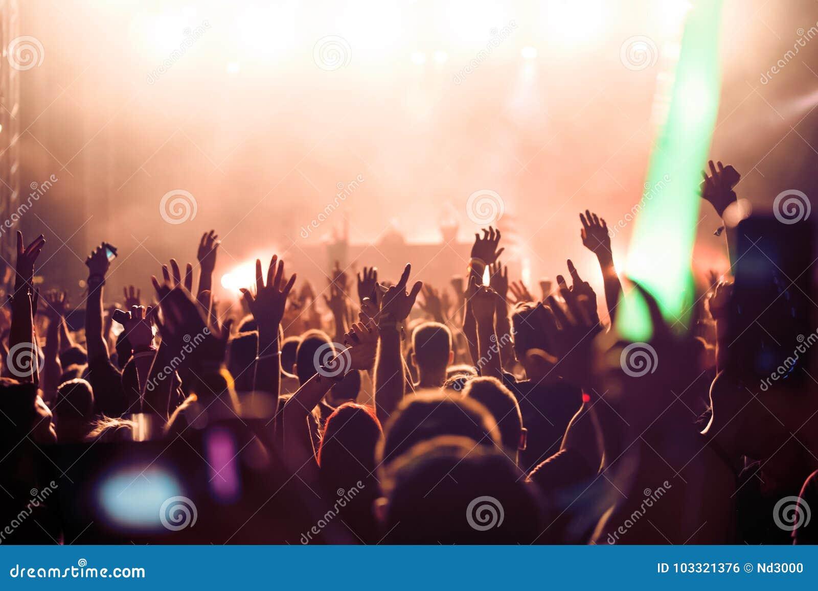 Het toejuichen van menigte met dient lucht bij muziekfestival in