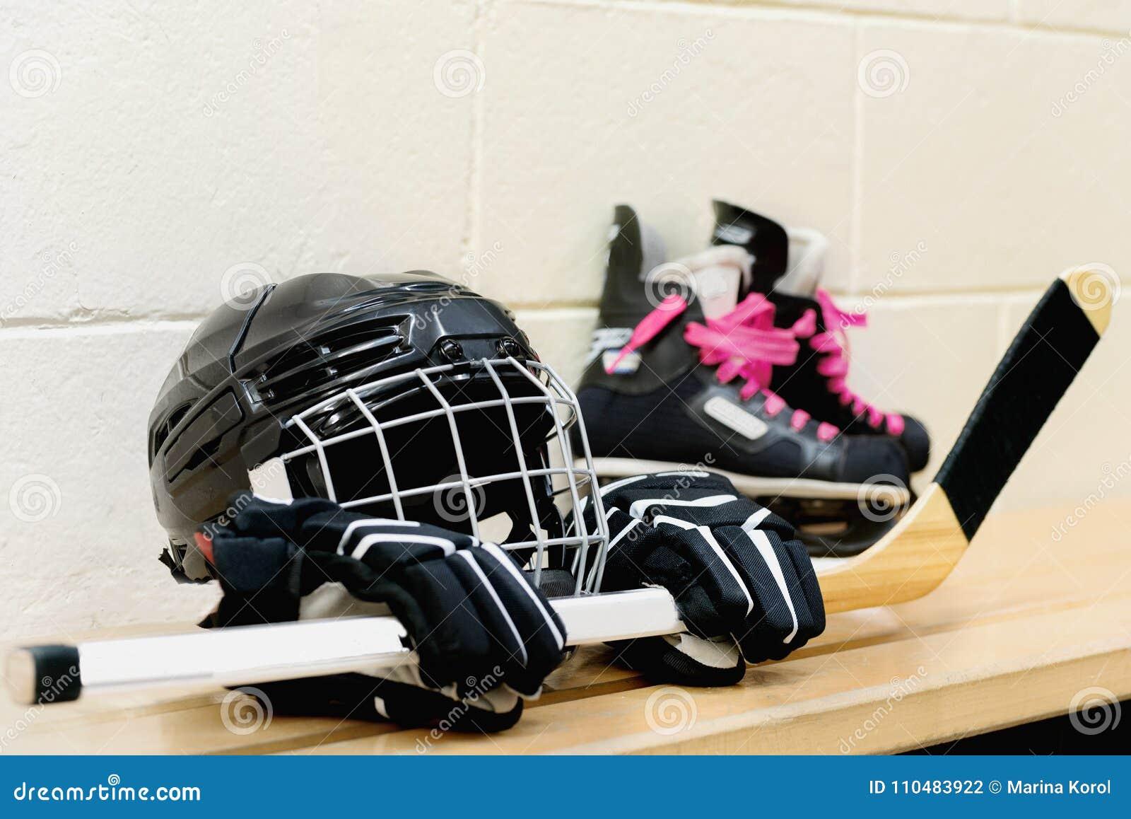 Het toestel van het meisjes` s hockey: helm, handschoenen, stokken, vleten met roze kant