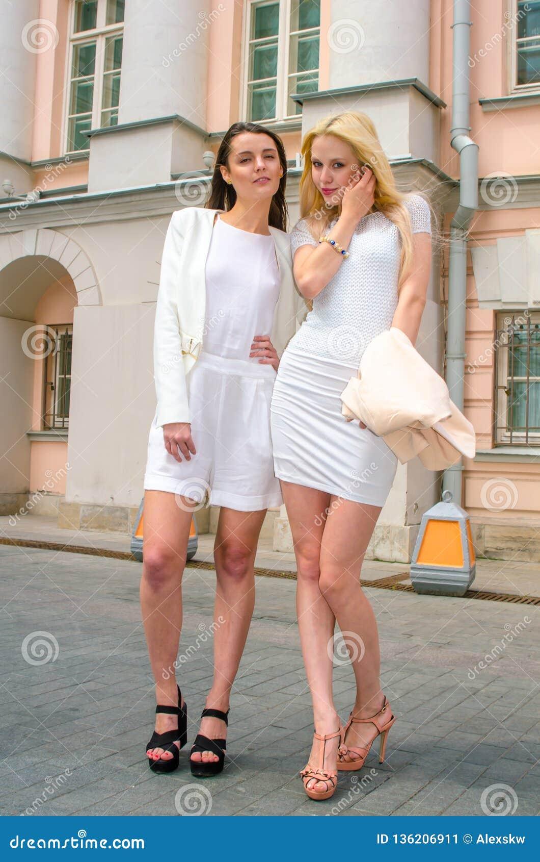 Het het twee vriendenblonde en brunette in wit kleden het stellen op de straat van de oude stad