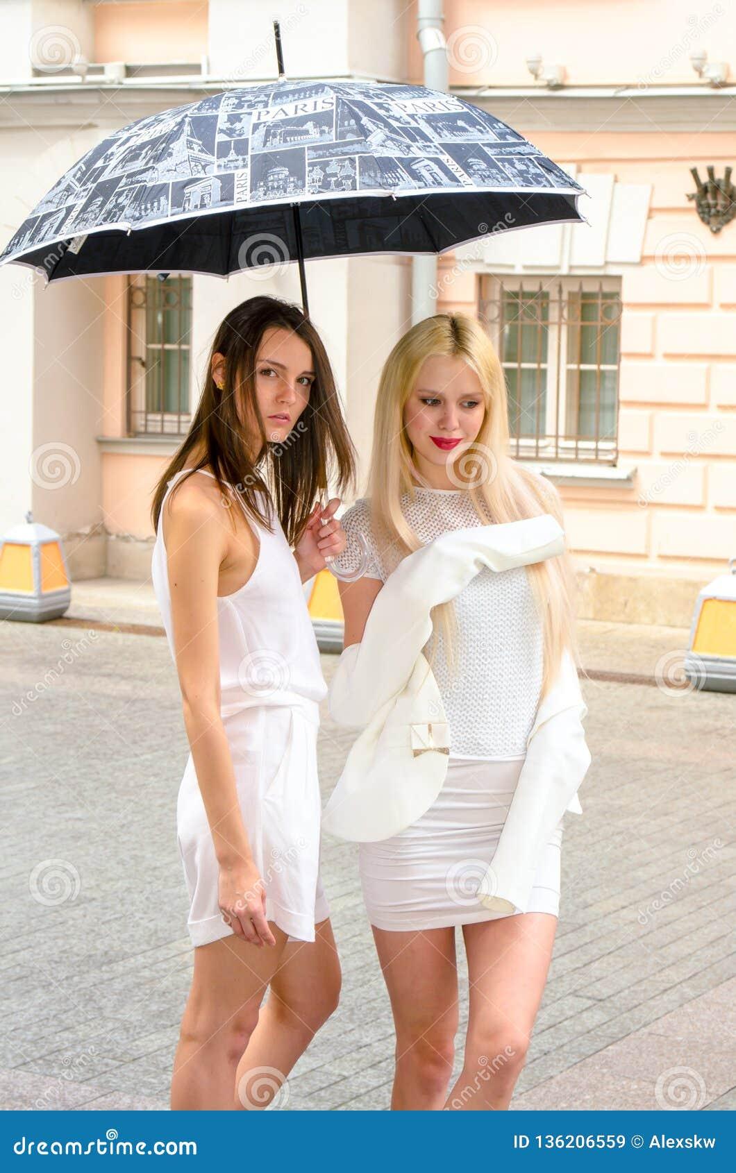 Het het twee vriendenblonde en brunette in wit kleden het verbergen van het weer onder een grote paraplu in de stegen van de oude