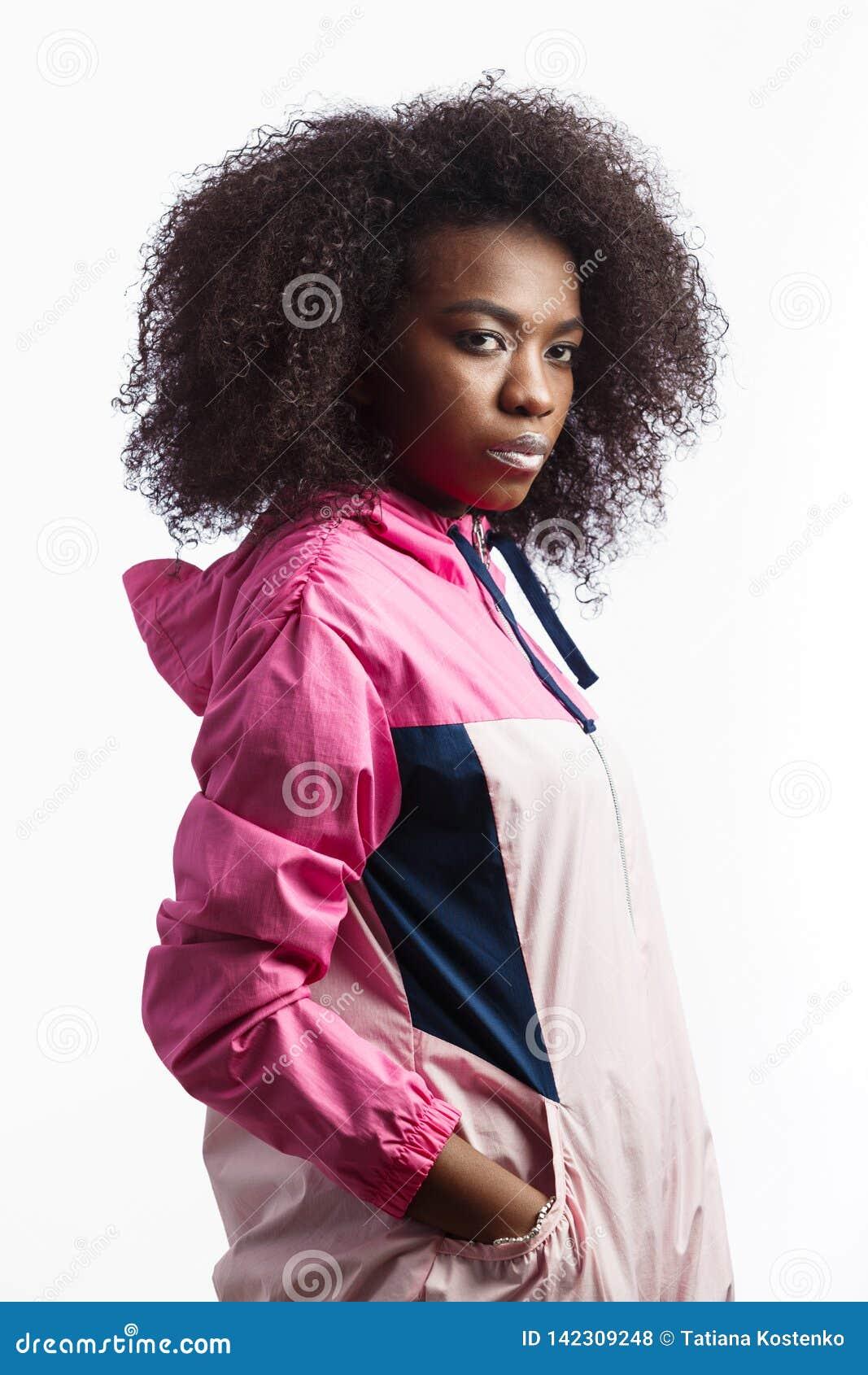 Het uitdagende jonge krullende bruin-haired meisje kleedde zich in de roze tribunes van het sportjasje bij de witte achtergrond i