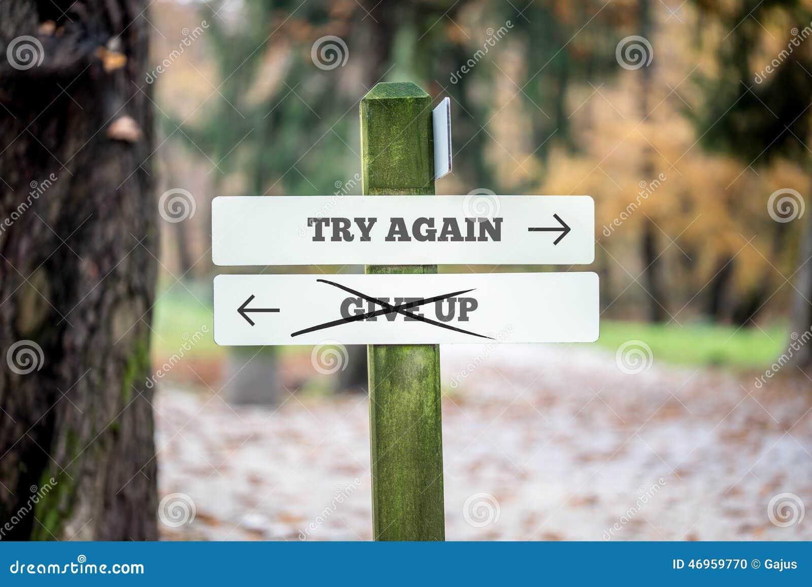 Het uithangbord met twee tekens die - probeer opnieuw zeggen - geeft - richtend op