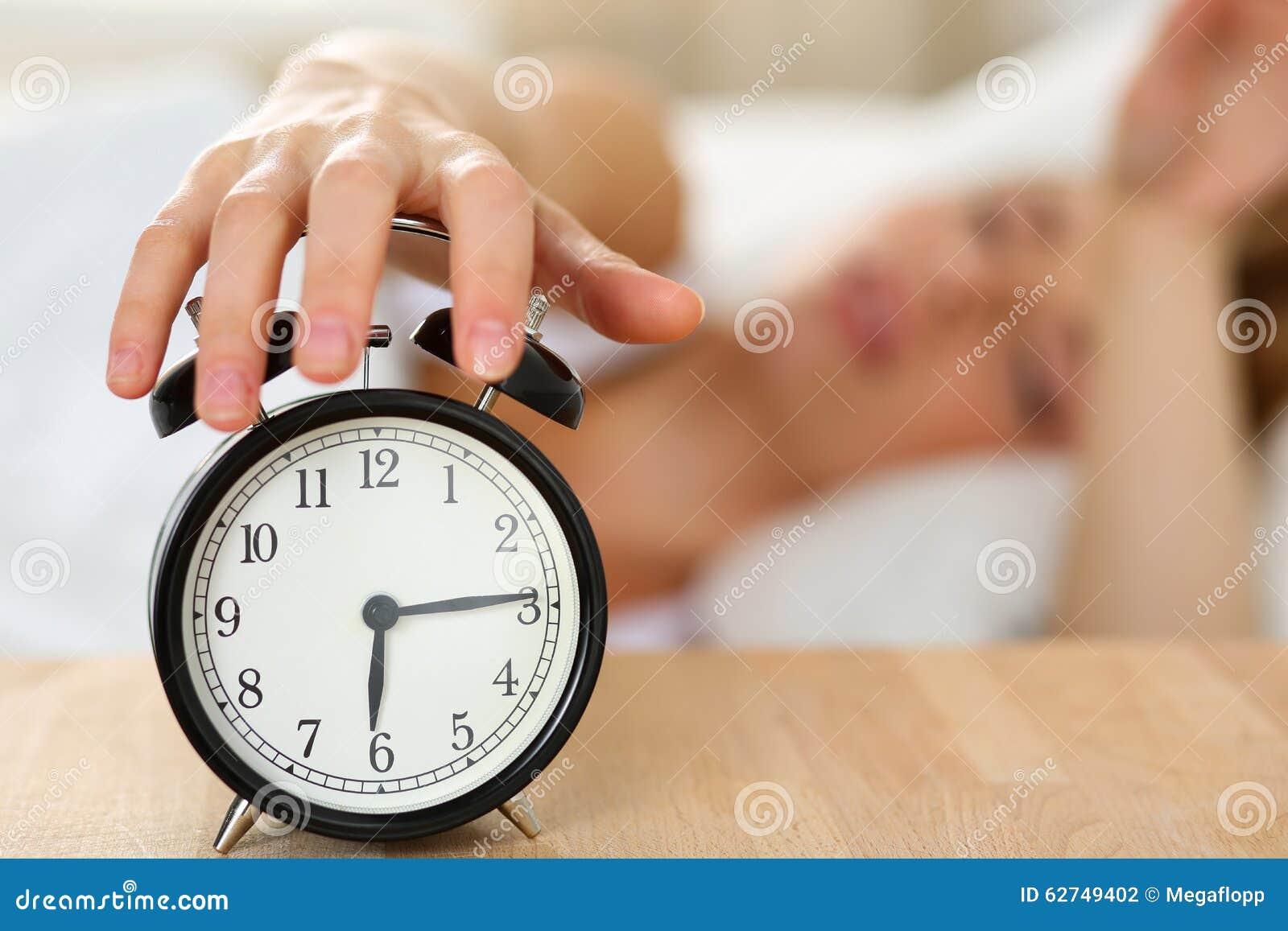 Het uitrekken van hand van slaperige jonge vrouw die dodenwekker proberen