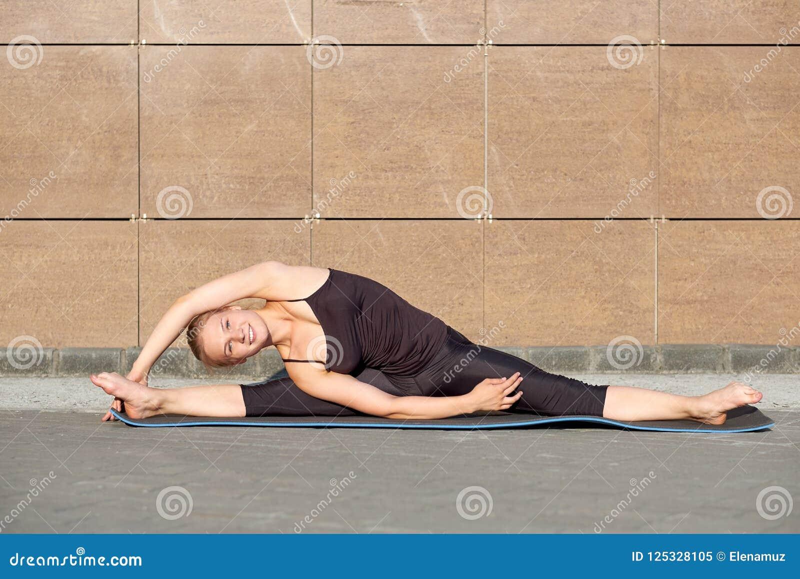 Het uitrekken van turnervrouw die spleet, streng op bruine stedelijke muurachtergrond doen