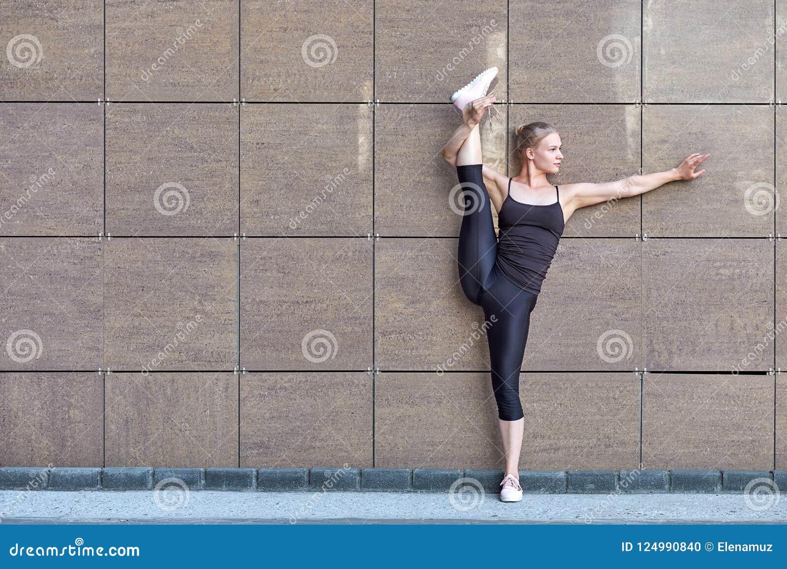 Het uitrekken van turnervrouw die verticale spleet, streng op bruine stedelijke muurachtergrond doen
