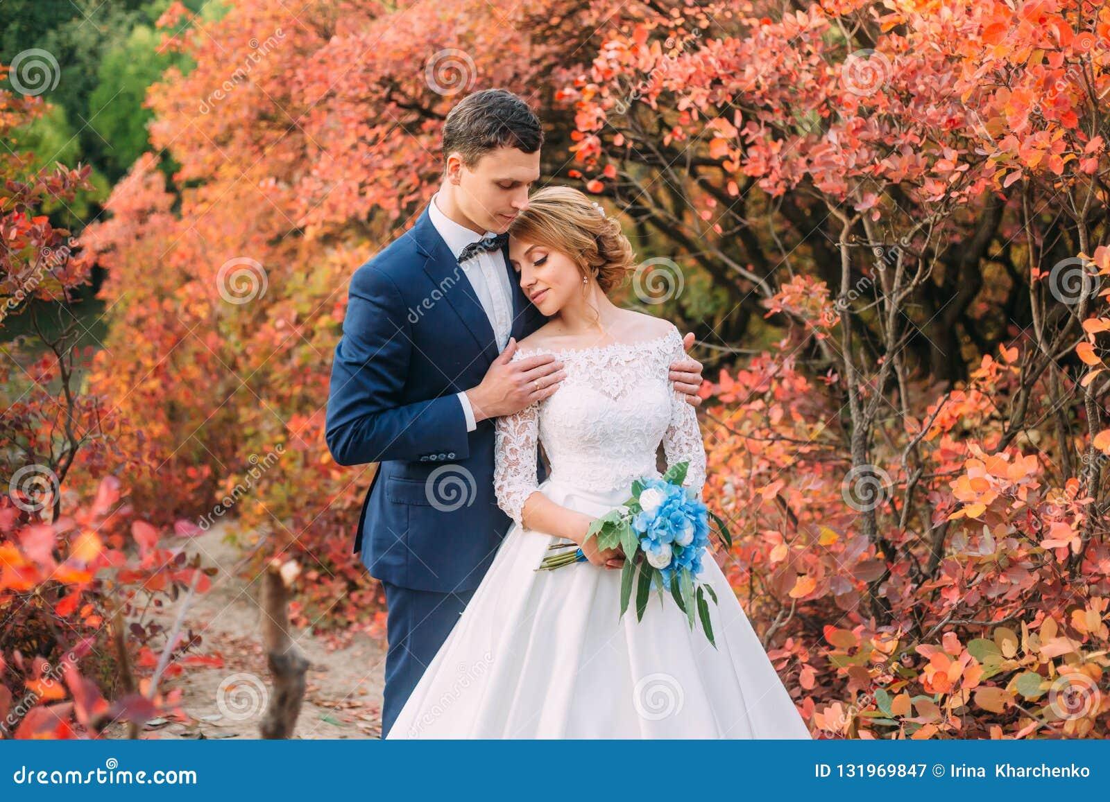 Het verbazen van aantrekkelijk jong paar in huwelijksdag bruid in elegante witte lange kleding en blauw boeket ter beschikking, d