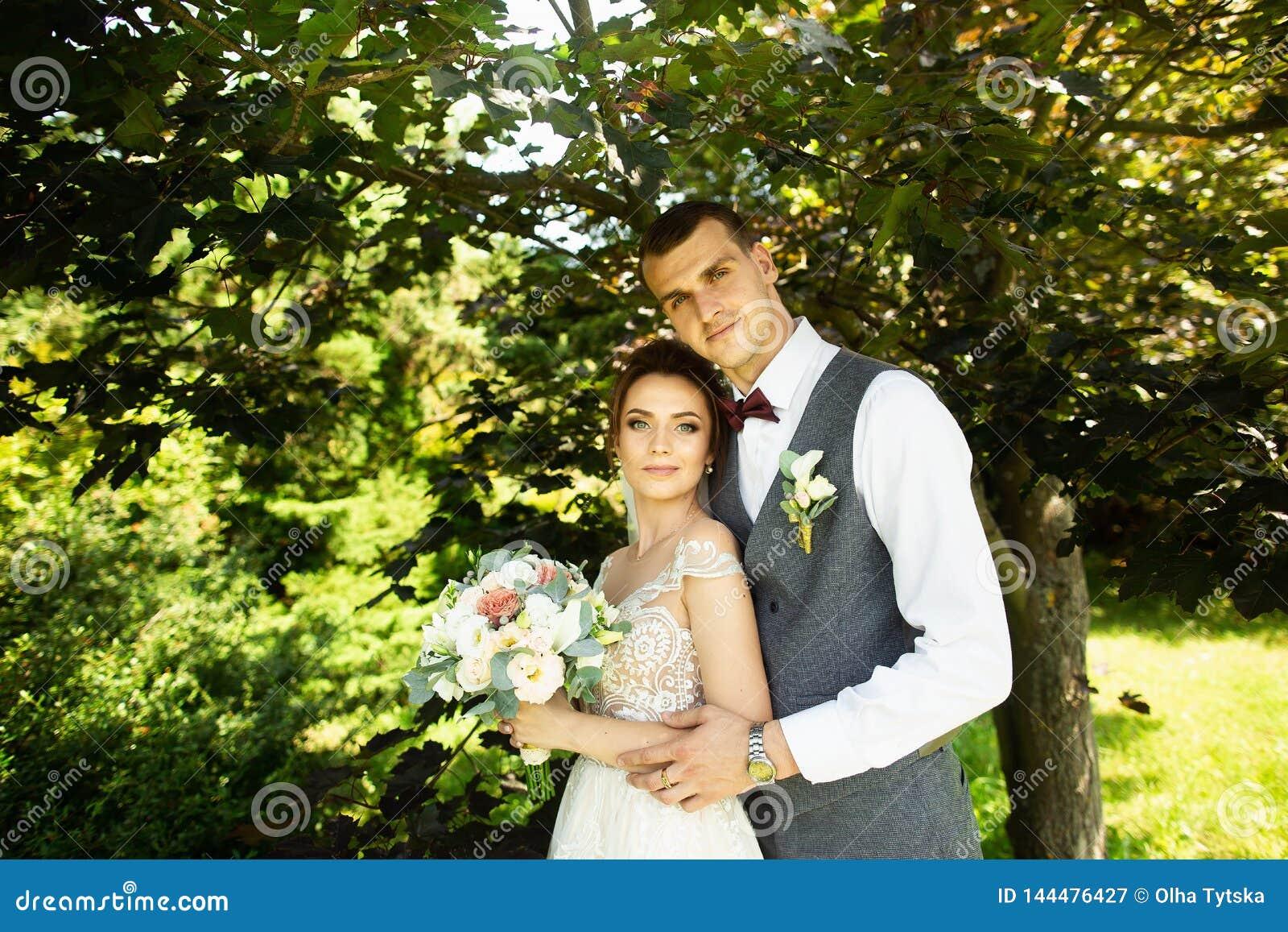 Het verbazende huwelijkspaar stellen op een groene natuurlijke achtergrond