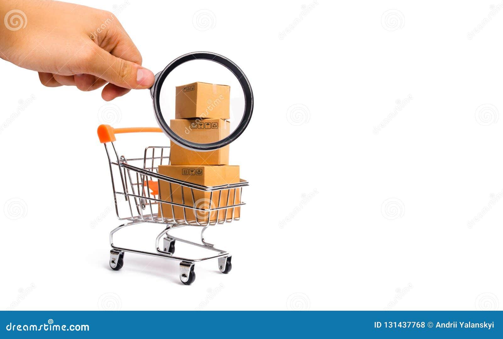 Het vergrootglas bekijkt de Supermarktkar met dozen, koopwaar: het concept het kopen van en het verkopen van goederen en diensten