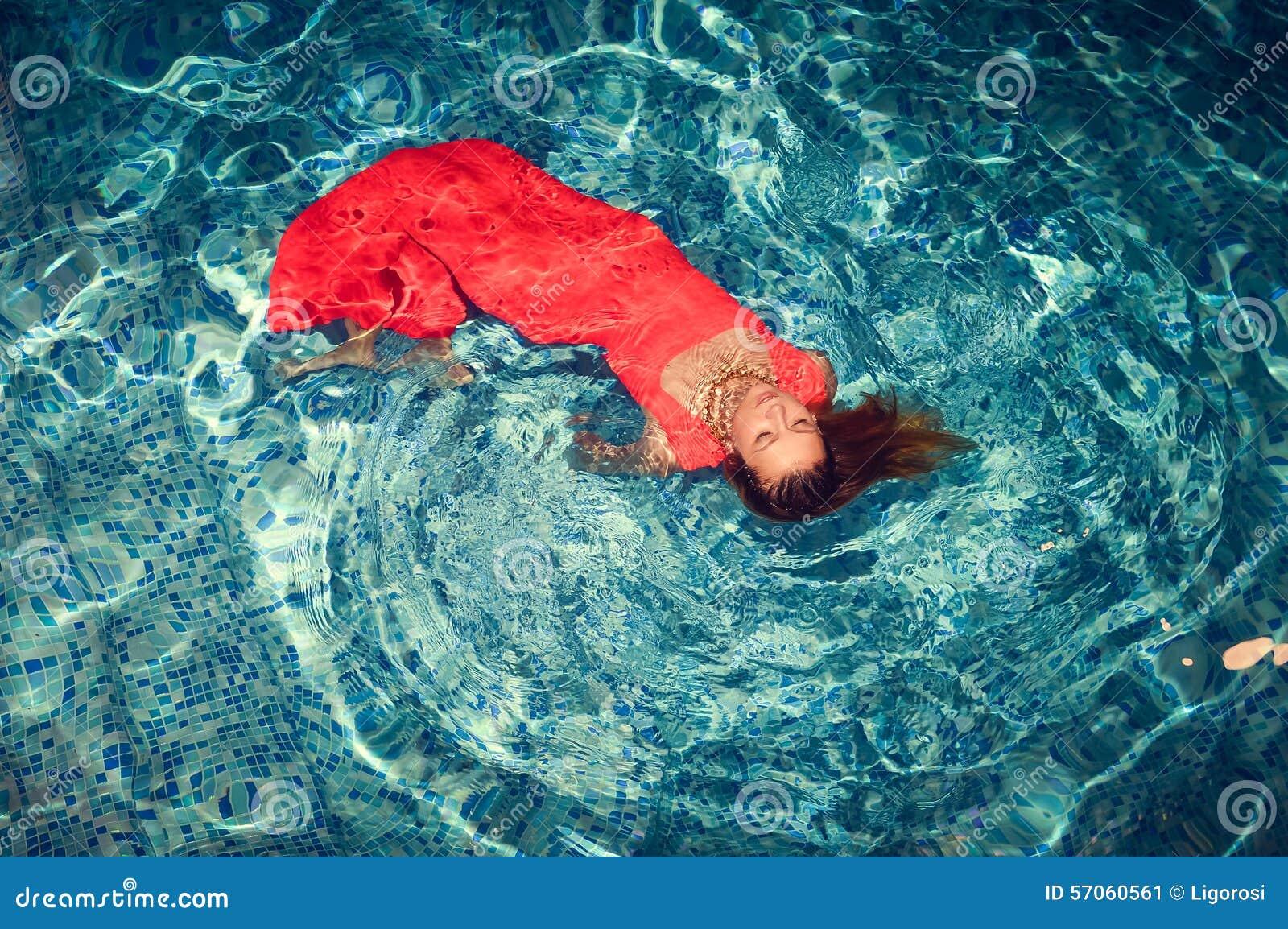 Het verleidelijke vrouwelijke binnen drijven op zwembad