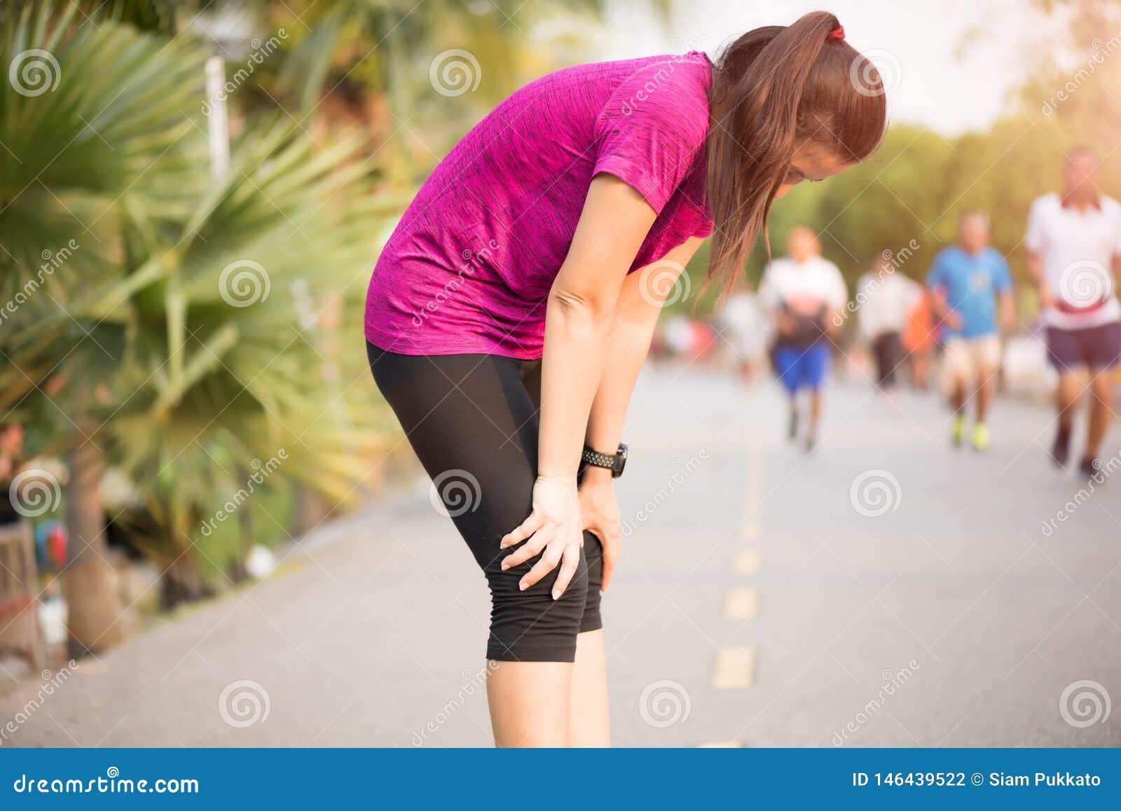 Het vermoeide Sportmeisje na het aanstoten of het lopen werkt in park uit Sport en gezondheidszorgconcept