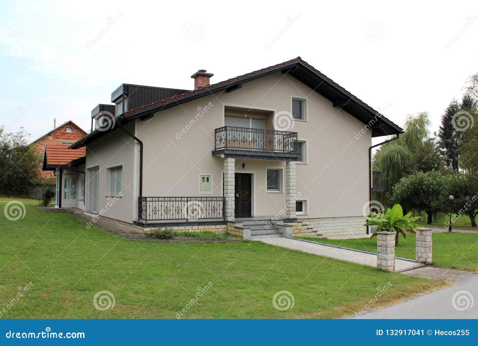 Het vernieuwde familiehuis in de voorsteden met voordiebalkon en steen betegelt ingang met vers gesneden groen gras en kleine pal