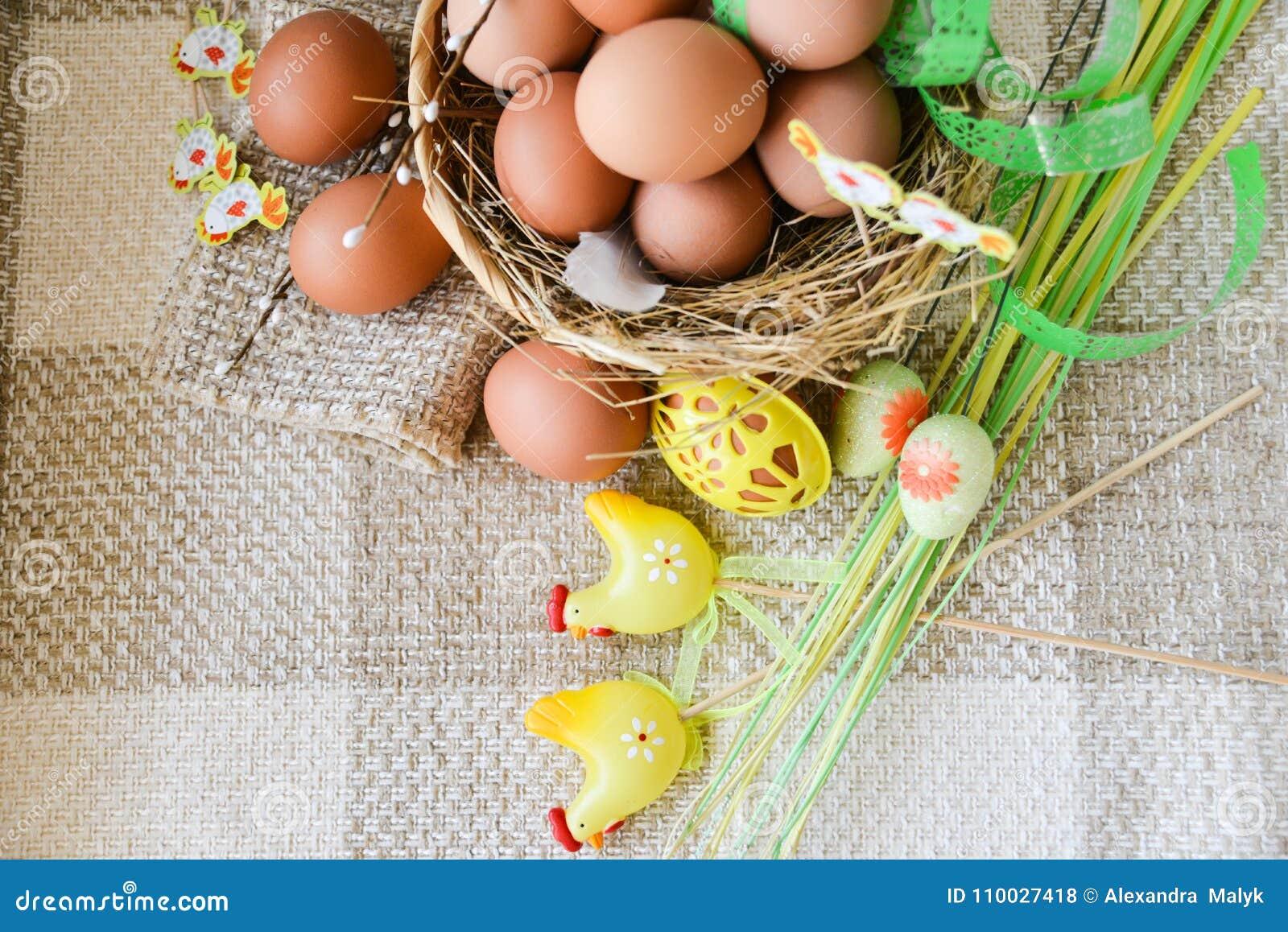 Het verse ei van de landbouwbedrijfkip in de mand op textielachtergrond, voorbereiding voor Pasen