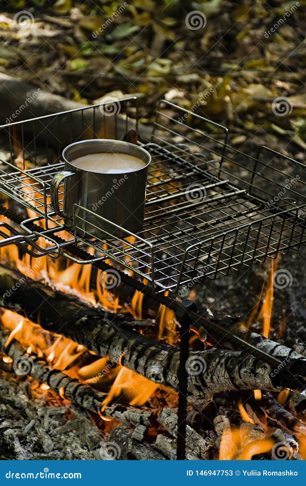 Het verwarmen van een kop van koffie terwijl het branden van een brand in een wild kampeerterrein
