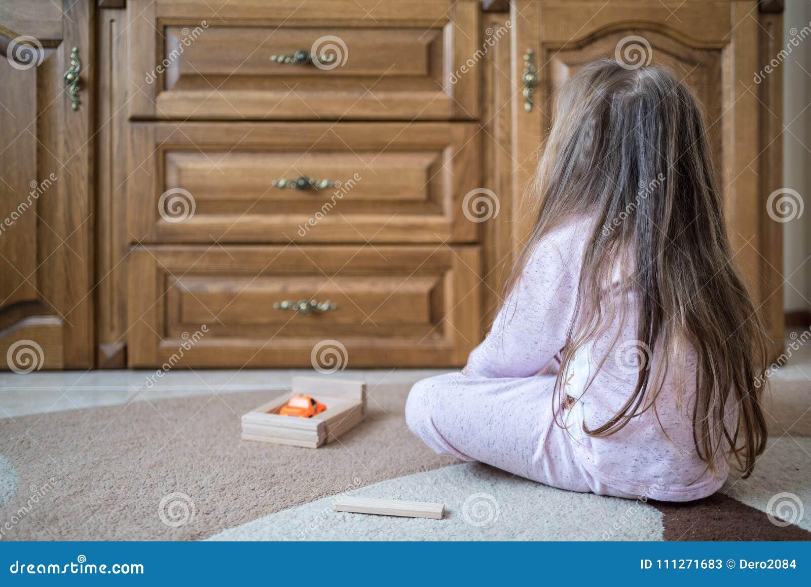Het vier éénjarigenmeisje in pyjama zit op tapijt, maakt garage voor stuk speelgoed auto gebruikend houten aannemer, zelfontplooi